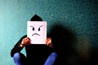 Mensch hält Papier mit unzufriedenem Smiley vors Gesicht - Das vierundachtzigste Problem