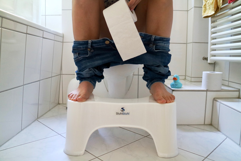 """Der """"StuhlStuhl"""" im Praxistest vor der Toilette mit Füssen und Schienenbeinen"""