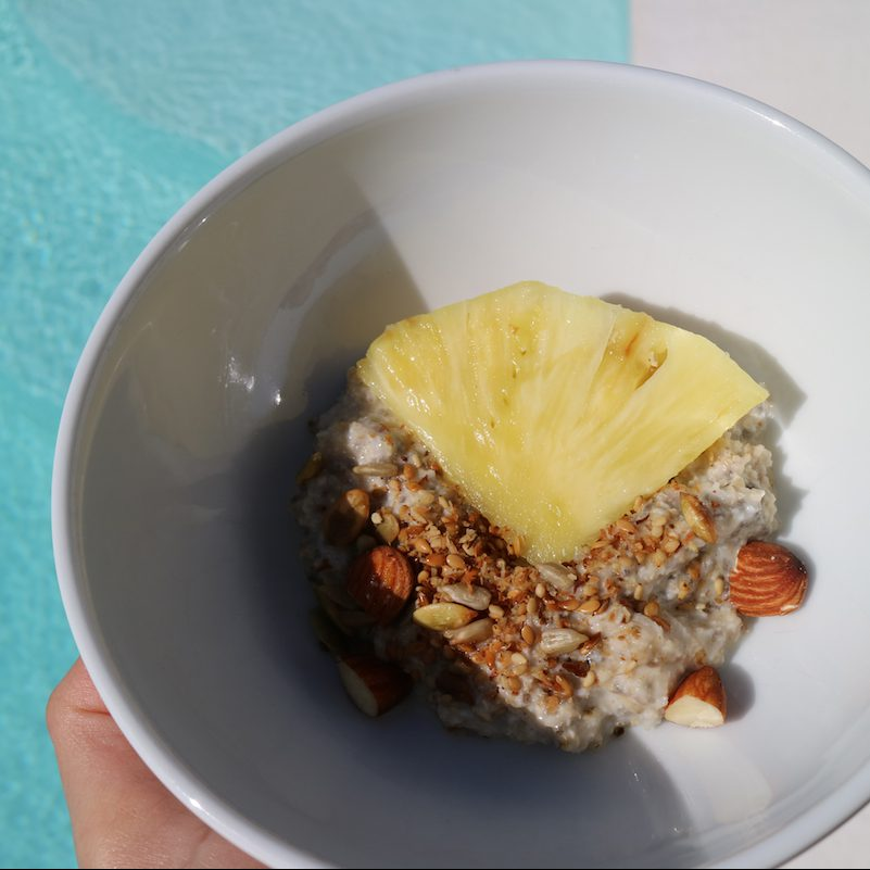 Müslischale mit Ananas, Pool im Hintergrund