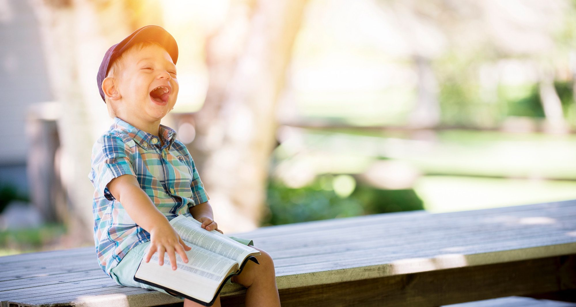 Lachendes Kind auf Tisch sitzend - sorgenfrei